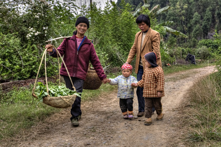 counterbalance: Yang Di village, Yangshuo, Guangxi, China - March 29, 2010: On country road in farmland is walking asian family, women and children, farmer carries on his shoulder a pole counterbalance to two baskets