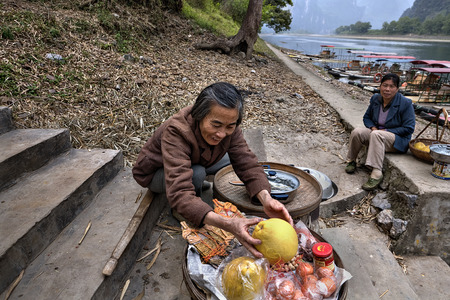tradeswoman: Yangshuo, Guangxi, China - March 29, 2010: Smiling elderly Asian woman farmer sells fruit on steps leading to pier on  background of bamboo rafts and Lijiang River, in  countryside of southern China.