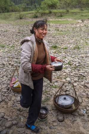 tradeswoman: Yang Di village, Yangshuo, Guangxi, China - March 29, 2010: Asian woman street vendor hot food holding a pot of food and smiling countryside in southern China, Guilin, spring.