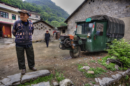 three wheeler: Fuli Village, Guangxi, China - March 30, 2010: Villagers in China, in countryside, rural Asian farmers, the elderly man and woman stand near stone farmhouses, next to old three-wheeled green truck.