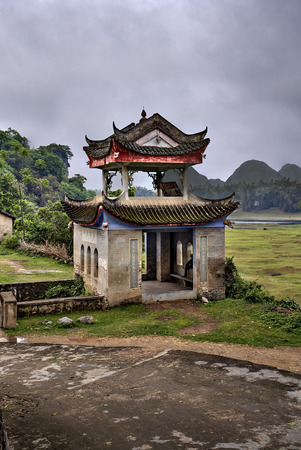 agricultural area: Fuli Village, Yangshuo, Guangxi, China - March 30, 2010: Stone pergola pagoda in picturesque agricultural area of rural China, amid the karst hills and grazing meadows, on edge ancient village spring. Editorial