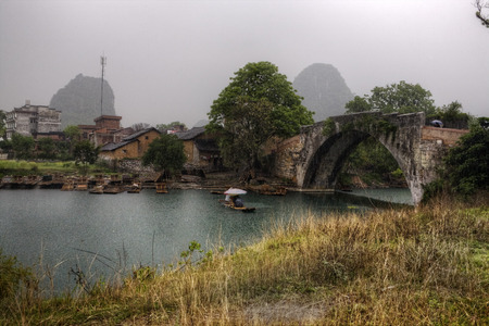 drench: Yangshuo, Guangxi, China - March 31, 2010: Dragon Bridge over Yulong River, Spring rain wets the tourists making a river cruise on a bamboo raft, the area of karst hills in the picturesque Guilin. Stock Photo