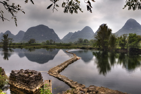 weir: The dam on the river Yulong in spring, at low water, amid the picturesque countryside of Guilin, with peaks of karst hills, Yangshuo County, Guangxi Province, southwest China. Stock Photo