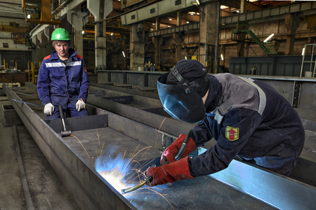 welds: St. Petersburg, Russia - May 18, 2015: Process gas welding at the plant for the production of bridge structures, welder welds to  jumpers bridge span girder bridge.