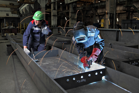 St. Petersburg, Russia - May 18, 2015: Steel sections of bridge span are manufactured  on plant metal structures production, welder uses gas torch for welding steel sheets, Gas metal arc welding, MIG.