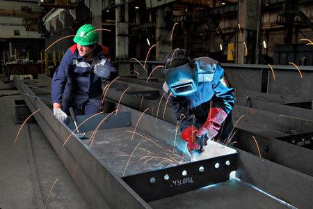 soldadura: San Petersburgo, Rusia - 18 de mayo 2015: Perfiles de acero de palmo puente se fabrican en la producción de estructuras metálicas de plantas, soldador utiliza la antorcha de gas para la soldadura de chapas de acero, soldadura por arco metálico con gas, MIG. Editorial