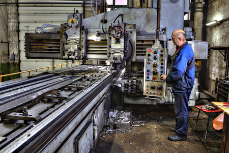machine operator: St. Petersburg, Russia - May 21, 2015: Heavy duty planer type milling machine for planing, grinding, milling, boring large metal parts, working machine operator controls the processing of metal.