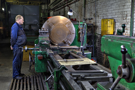 metal processing: St. Petersburg, Russia - May 21, 2015: Metal processing on a large lathe, turner machine operator controls the process, turning shop at the plant of metal constructions.