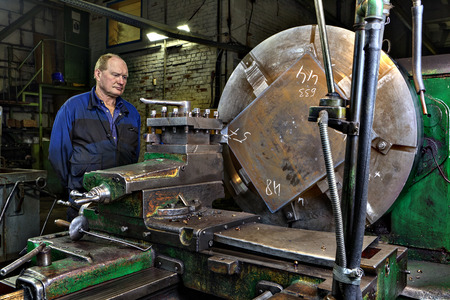 tool chuck: St. Petersburg, Russia - May 21, 2015: Master turner machine operator controls the processing of a large steel billets the big green lathe, Machinery equipment shop at a steel plant.