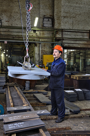 loads: St. Petersburg, Russia - May 21, 2015: The operator lifting device, lift loads using lifting magnet, mechanical workshop, metal structures plant.