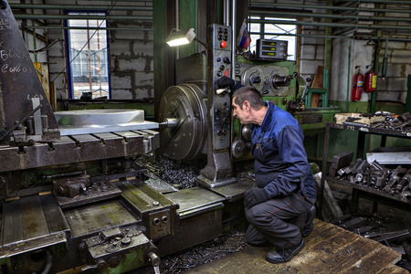 machinetool: St. Petersburg, Russia - May 21, 2015: The operator controls the process of drilling the metal part on the horizontal boring machine.