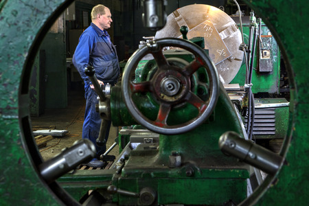 machine operator: St. Petersburg, Russia - May 21, 2015: Processing of steel parts on a large lathe, turner machine operator controls the process, machine tool workshop in the factory of steel structures.