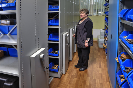 storekeeper: St. Petersburg, Russia - May 21, 2015: Mobile Compactor Storage System on rails, Toolroom, Woman storekeeper moves mobile shelving storage of tools on  guide paths.