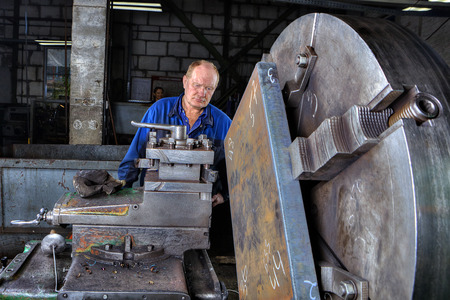 Saint Petersburg, Russia - May 21, 2015: Machine tool operator handles steel billet clamped in a large jaw chuck, big lathe in the factory of metal constructions.