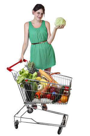 19 years: Smiling Caucasian girl in a green dress 19 years old holding a cabbage standing near a shopping cart filled with food isolated on a white background, saved path selection. Stock Photo