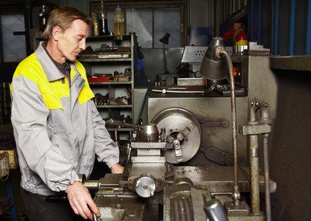 St. Petersburg, Russia - 22 December 2011: Turner grinds steel part on a lathe.