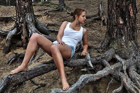 16 years: Young teenager girl in shorts and a white T-shirt, lying on the roots of a tree in a pine forest.