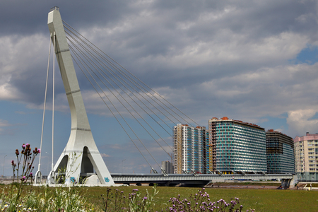 mains: St. Petersburg, Russia - July 9, 2015: Single-span cable-stayed bridge with one pylon, Suspension bridge with a heating mains, guyed crossing, across the river in a residential area.