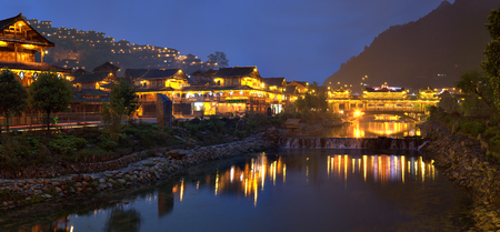 miao: Xijiang miao village, Guizhou Province, China - april 18, 2010: Large the Miao ethnic minority village at night illuminated wooden buildings are reflected in the river night lights. Editorial