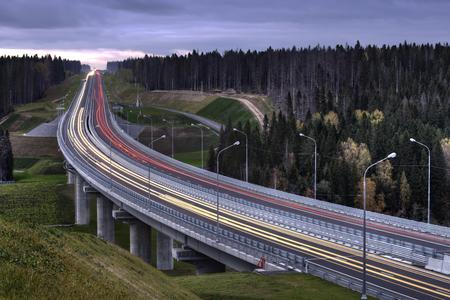 hormig�n: La luz arrastra la autopista sin peaje en el bosque ruso oto�o despu�s de la puesta del sol.