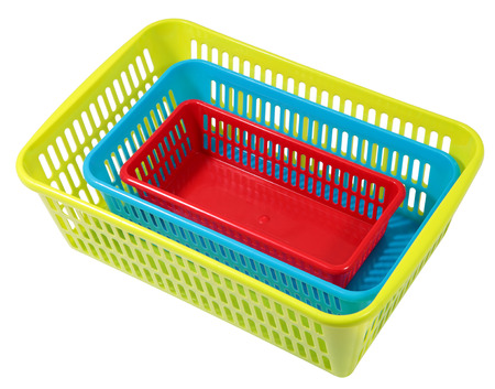 another: Nested in one another, different size and different colored, perforated plastic boxes, storage systems for domestic use, isolated on white.