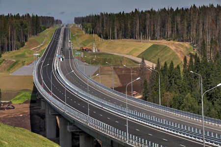 top 7: Saint Petersburg, Russia - August 7, 2015: Top view of highway bridge in final stage of construction, and a high-speed road in the forest. Leningrad Region, new motorway in  direction of Sortavala.