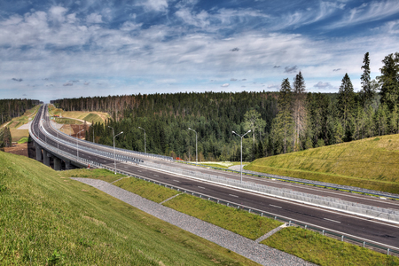 itinerary: Saint Petersburg, Russia - August 7, 2015: Speedway in the Leningrad region, new  Priozersk highway, drainage ditches for storm water before the bridge over the river Smorodinka.