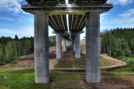 riverbed: Saint Petersburg, Russia - August 7, 2015: Bottom view on steel bridge spans the highway bridge on concrete supports crossing the riverbed. A highway crosses forest, in North-West region of Russia.