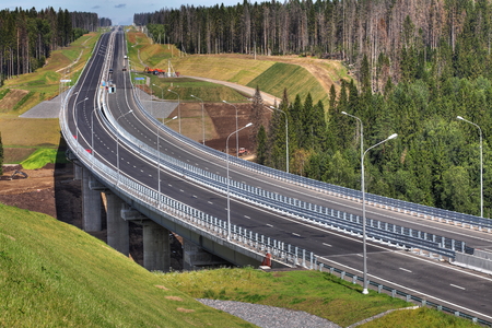 autobahn: Saint Petersburg, Russia - August 7, 2015: The expressway crosses the forest, steel trestle bridge is supported by reinforced concrete supports.