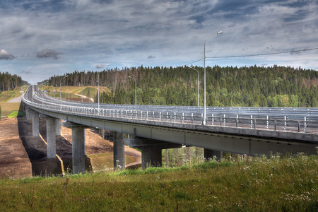 span: Saint Petersburg, Russia - August 7, 2015: Concrete support supporting steel structures span road bridge, on the four-lane highway in a dense forest.