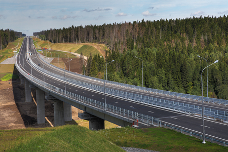 express lane: Saint Petersburg, Russia - August 7, 2015: Four-speed road through the forest, and a steel motor road bridge on reinforced concrete piers, Priozersk district, Leningrad region, highway Sortavala.