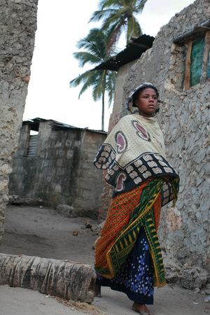 Zanzibar, Tanzania - 20 februari 2008: Unknown blootvoets donkere huid Afrikaanse moslim meisje in hoofddoek, is op een smalle straat vissersdorp.