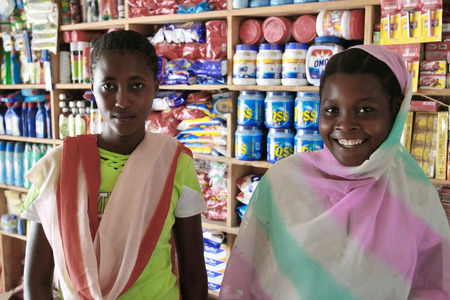 headcloth: Zanzibar, Tanzania - February 18, 2008: Two young African women saleswoman at the store household goods.