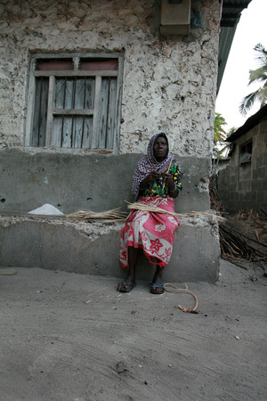 kindling: Zanzibar, Tanzania - February 20, 2008: Elderly African woman sitting near the stone house, and cuts the chips for kindling fire.