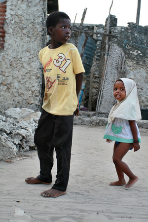Zanzibar, Tanzania - February 20, 2008: Unidentified African children Muslims, walk the fishing village, a boy about 8 years old, and a girl about 4 years old.