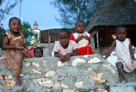 extramural: Zanzibar, Tanzania - February 19, 2008: Group of young African children, black boys and girls playing in the yard in the evening, a fishing village on the island of Zanzibar, East Africa.