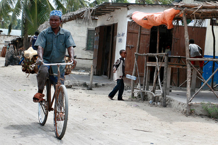 east africa: Zanzibar, Tanzania - February 18, 2008: Unknown black African men in the Arab skullcap, riding a bicycle on a dusty street in the fishing town.