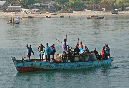 leeway: Zanzibar, Tanzania - February 16, 2008: Many African men standing in a blue boat floating along the shore.
