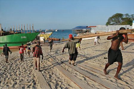 Zanzibar, Tanzania - February 16, 2008: African longshoremen unload a Lumber boat in the port of Zanzibar.