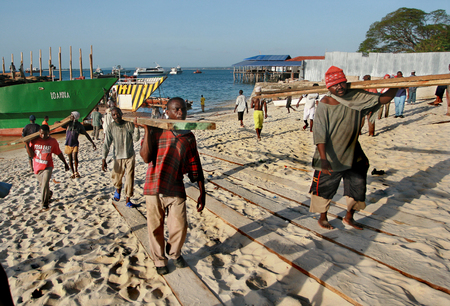 unload: Zanzibar, Tanzania - February 16, 2008: African stevedores unload a timber ship in the harbor of Zanzibar.