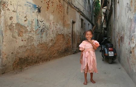 16 years: Zanzibar, Tanzania - February 16, 2008: Unknown smiling African girl with braids around 6 years old, standing near the old dilapidated, stone houses. Editorial