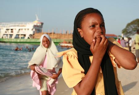 Zanzibar, Tanzania - February 16, 2008: Two unidentified african Muslim woman, about 10 years old, walking along the beach near the port.