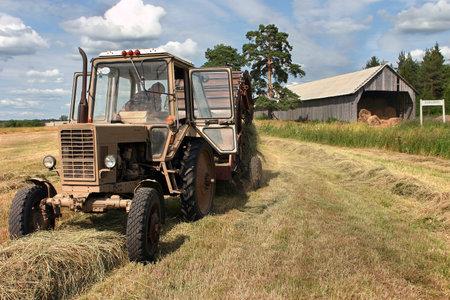 baler: Lemozero, Olonets, Karelia, Russia - July 26, 2006: Harvesting of hay for farmland in the Russian north, round hay baler hooked to farm tractor. Editorial