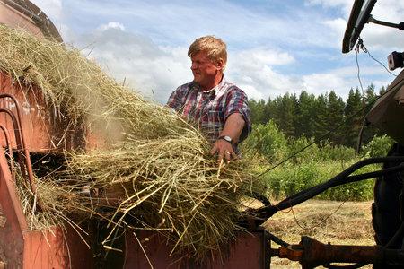 haymaking: Lemozero, Olonets, Karelia, Russia - July 26, 2006: Haymaking time, Russian farmer repair round baler, harvests hay.