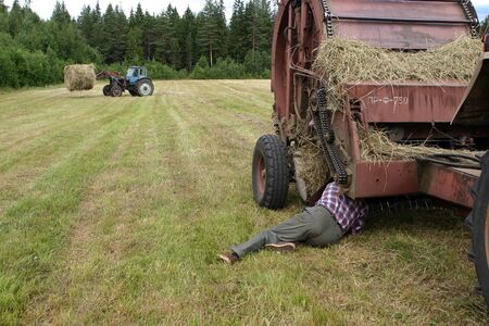 agriculturalist: Lemozero, Olonets, Karelia, Russia - July 26, 2006: Driver of tractor repair round baler in the field.
