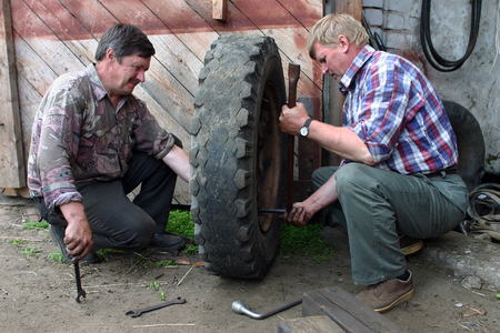 tire fitting: Lemozero, Olonets, Karelia, Russia - July 26, 2006: Two farmers car mechanics, tire making, in the courtyard of repair shop.