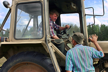 agriculturalist: Lemozero, Olonets, Karelia, Russia - July 26, 2006: Farmer tractor driver sits in the the tractor cab, and talking with the peasant, who is standing near the tractor. Editorial
