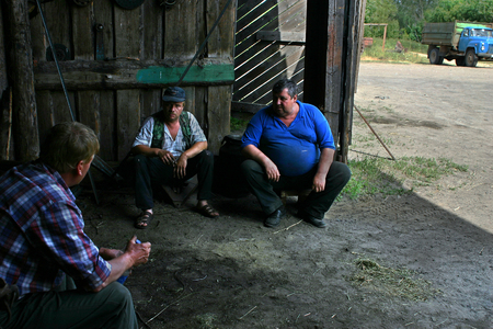 peasant farming: Lemozero, Olonets, Karelia, Russia - July 26, 2006: Agricultural work during the harvest of hay, three farmers were hiding from the sun in the shade of a wooden barn during a short break in the work. Editorial
