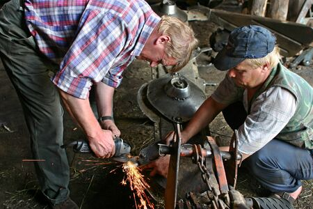agriculturalist: Lemozero, Olonets, Karelia, Russia - July 26, 2006: Two farmers farm tractor mowing-machine repaired in a repair shop, sharpening knives using a grinding machine. Editorial