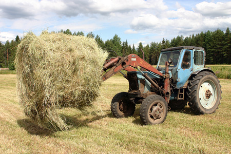 peasant farming: Lemozero, Olonets, Karelia, Russia - July 26, 2006: Farmers tractor gathering round hay bales.